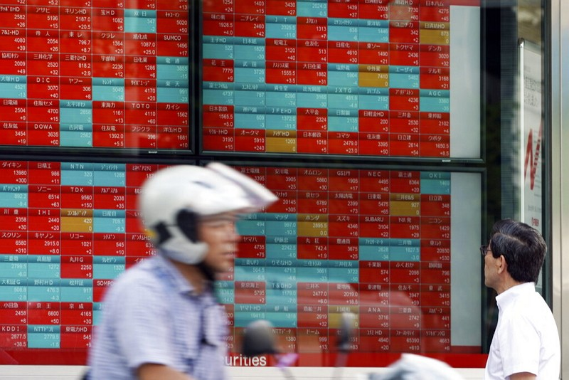 A man looks at an electronic stock board showing Japan's Nikkei 225 index. (AP photo)
