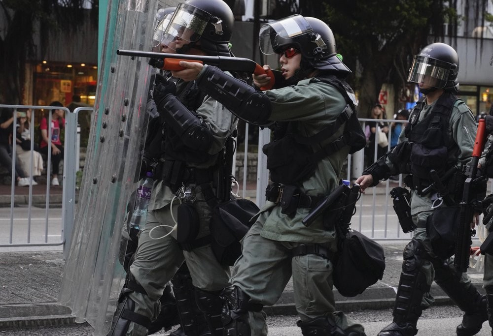 A police officer pointing his weapon at protesters in Hong Kong Saturday September 21.