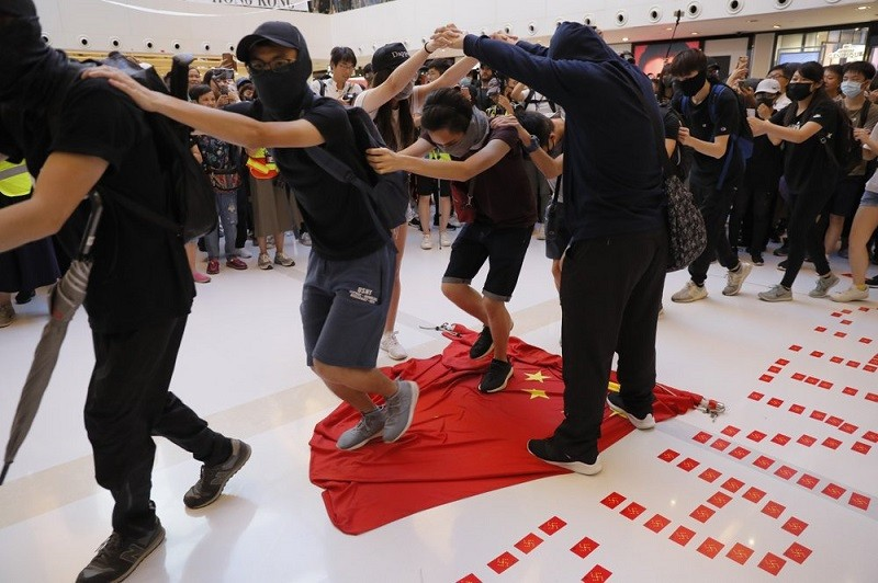 Protesters walk on a Chinese national flag during a protest at a mall in Hong Kong on Sunday, Sept. 22, 2019. (AP photo)