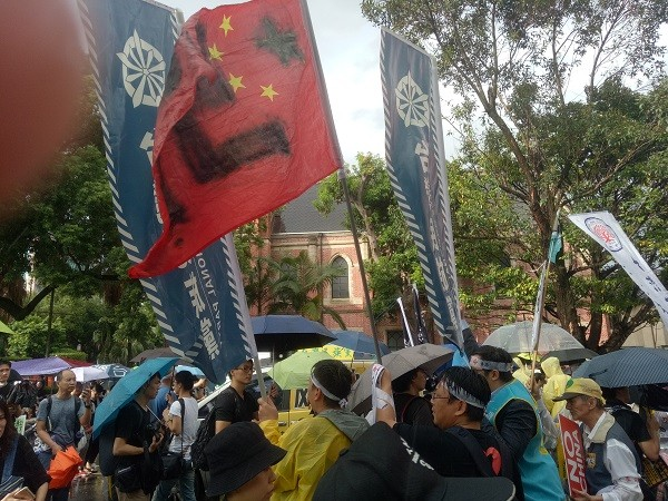 "Anti-China protesters wave ""Nazi"" China flag."