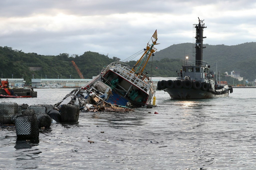 One of the fishing trawlers hit by the collapsed bridge was being towed away Tuesday afternoon.