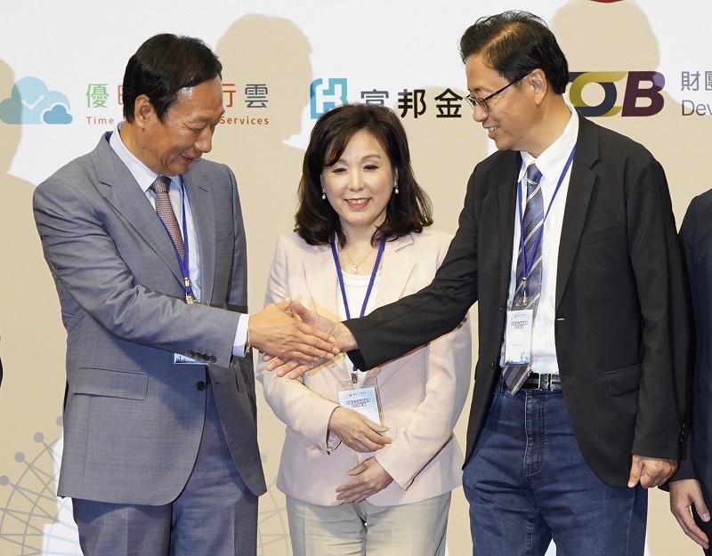 郭台銘(左)在玉山科技協會理事長李紀珠(中)安排下,與前行政院長張善政(右)握手合影。中央社