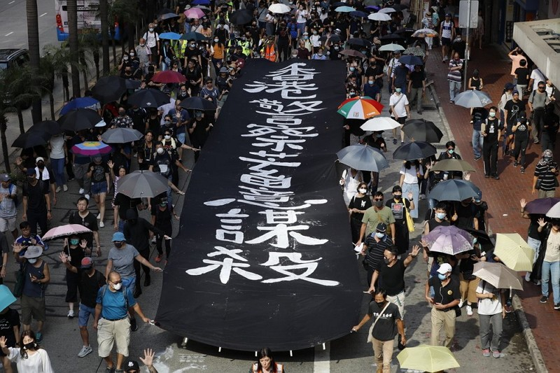 Masked protesters walk next to a banner that reads 'Hong Kong police deliberately murder.' (AP photo)
