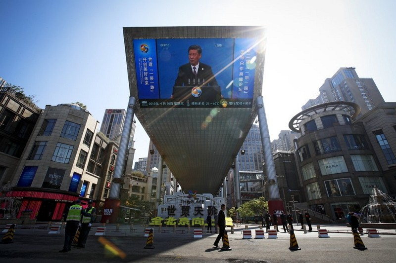 Traffic warden and securities stand guard near a TV screen broadcasting live of Xi Jinping's opening speech, outside a shopping mall in Beijing (AP ph...