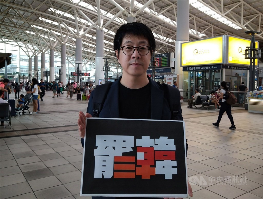 Co-initiator Aaron Yin with a 'Recall Han' poster.
