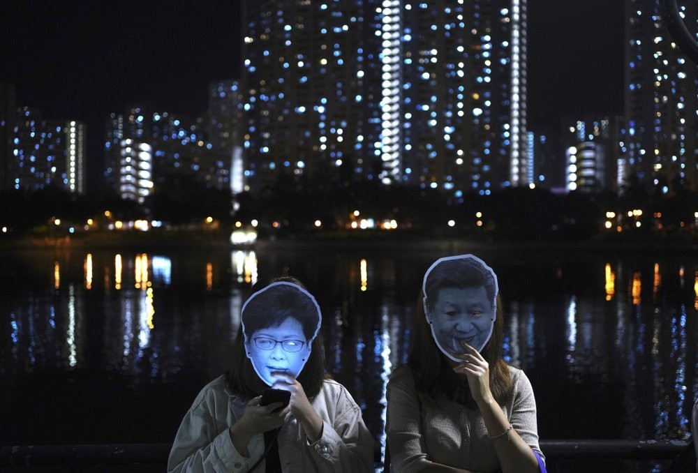 Demonstrators wearing masks of Carrie Lam (L) and Xi Jinping (R), Oct. 18