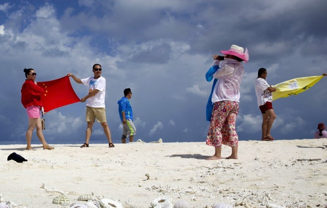 Chinese tourists pose with flag on Quanfu Island.