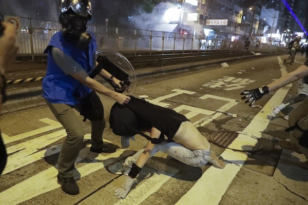 Cop strips top off female Hong Kong protester