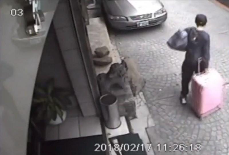 圖為陳同佳推著粉紅色皮箱離開飯店的監視器畫面 (中央社)