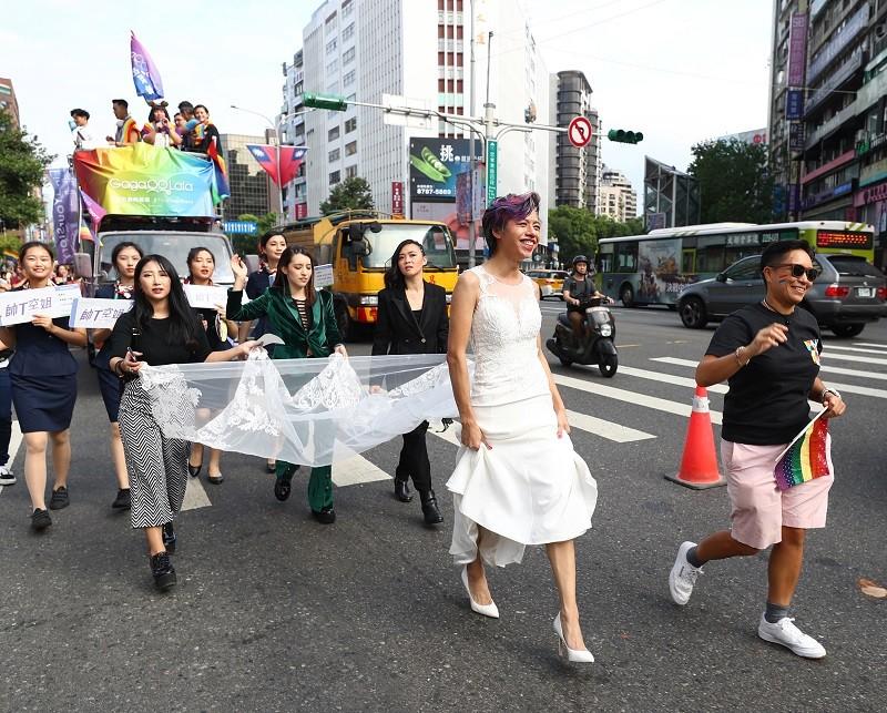 今年遊行主題為「同志好厝邊」,有人特別精心打扮,穿婚紗參與遊行。中央社