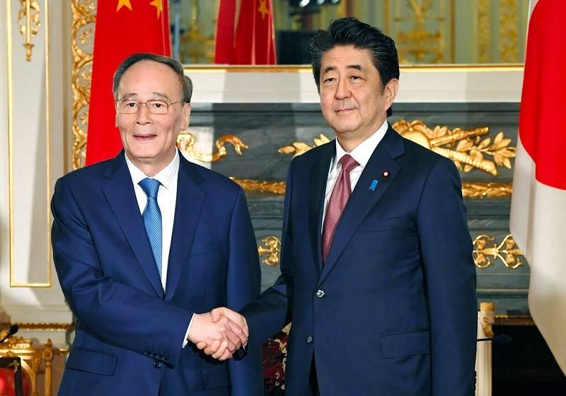 安倍晉三(右)23日會晤來訪的中國國家副主席王岐山(左)時,曾特別提到日本學者遭拘留一事。美聯社