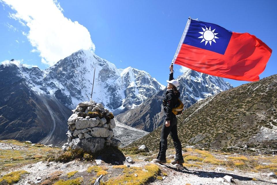 Female psychiatrist in bikini waves Taiwan flag at Everest base camp