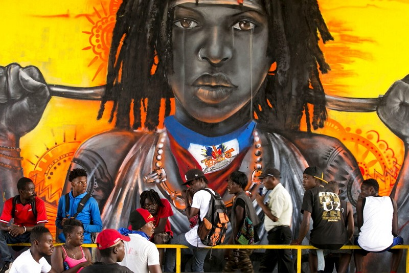 Protesters gather in front of a mural, in Haiti.