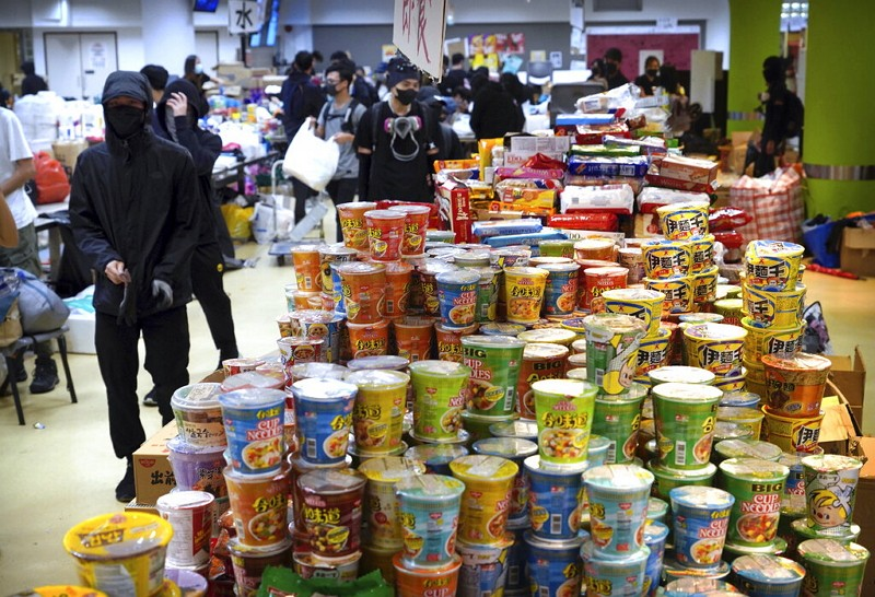 Protesters walk past stacks of instant noodles in a canteen at Hong Kong Polytechnic University.