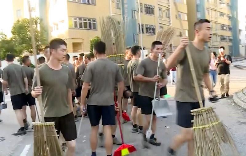 駐港解放軍帶著掃把幫忙清掃街頭 (美聯社)