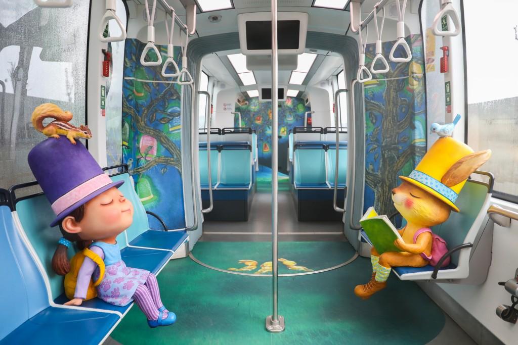 淡海輕軌通車週年幾米主題列車26日正式上線服務,列車裡還有可愛的實體繪本主角娃娃,讓遊客彷彿走入幾米的繪本世界裡。(圖/新北捷運公司)