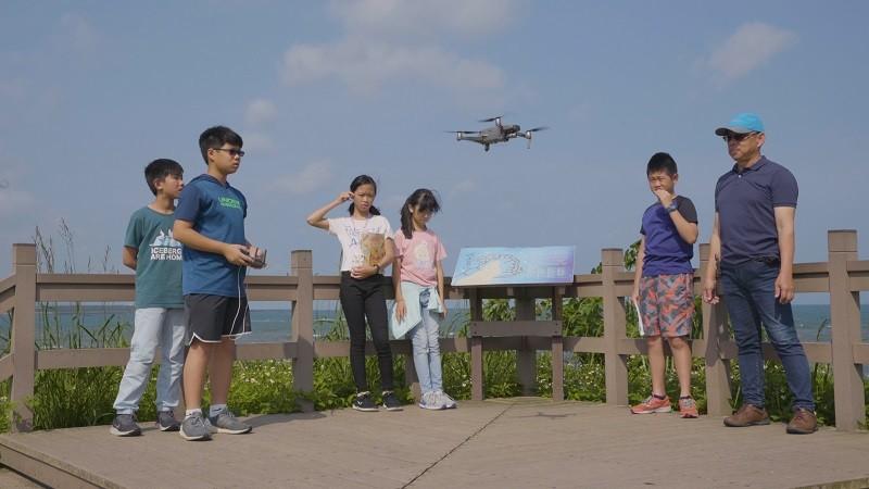 王世杰和學生們在海邊進行空拍機的操作。(國家教育研究院圖片)