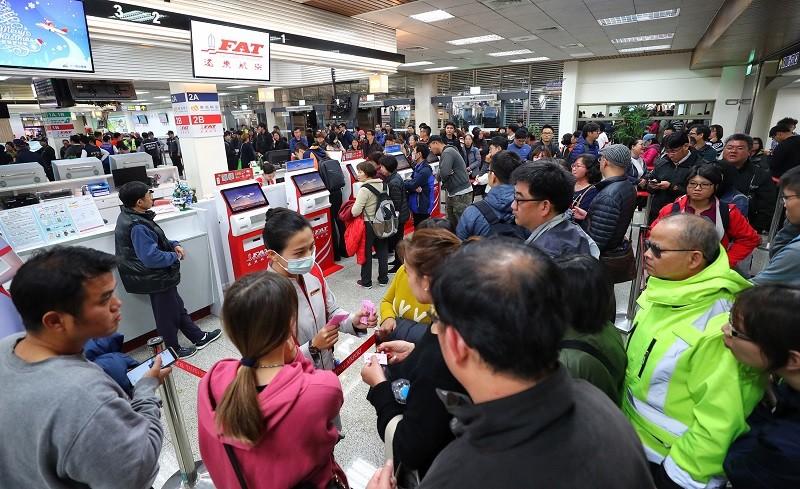 台北松山機場遠航櫃檯12日湧現人潮,大批民眾詢問及辦理退票作業。中央社