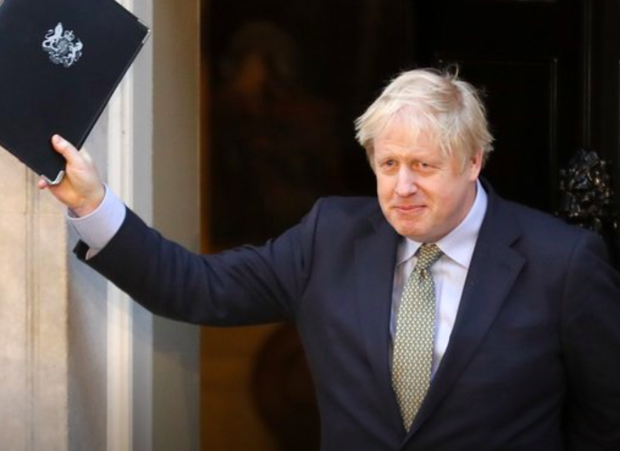 Britain's Prime Minister Boris Johnson waves after addressing the media outside 10 Downing Street in London on Dec. 13. (Courtesy of AP)