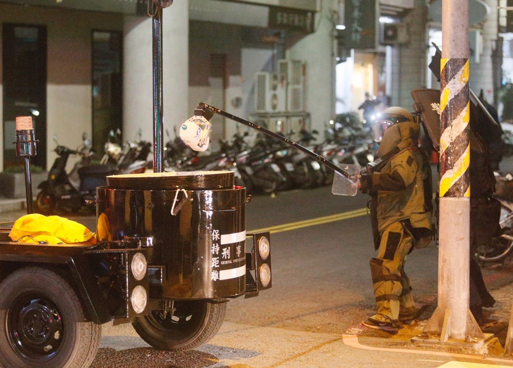 A bomb disposal expert tackles a bottle thrown into the street by the suspect.