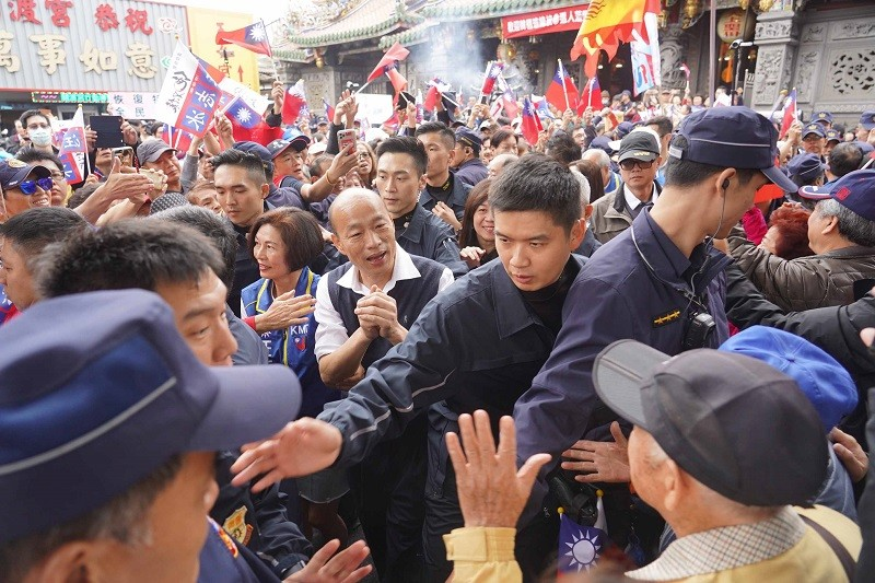 國民黨總統候選人韓國瑜(中)22日陪同立委參選人汪 志冰在台北市關渡宮參拜造勢,向支持者拱手致意。中央社