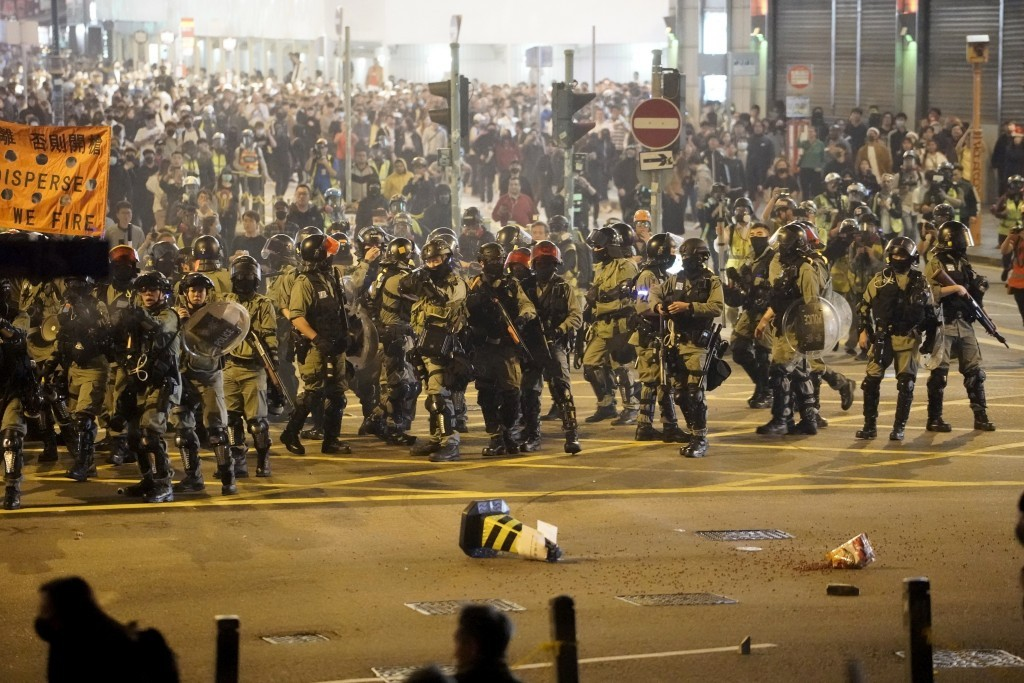 Hong Kong police prepare to deploy tear gas canisters.