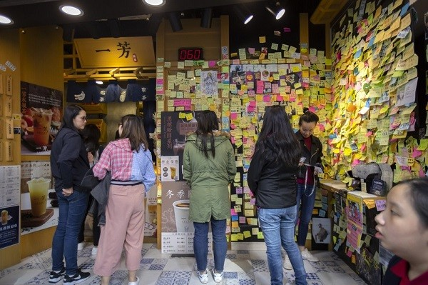 Customers line up at a tea store with pro-protest notes in Hong Kong.
