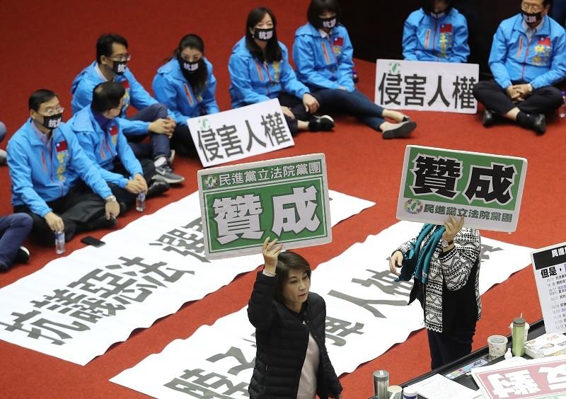 國民黨立委坐在議場中,對《反滲透法》表達反對立場,民進黨團則舉牌表示贊成。中央社