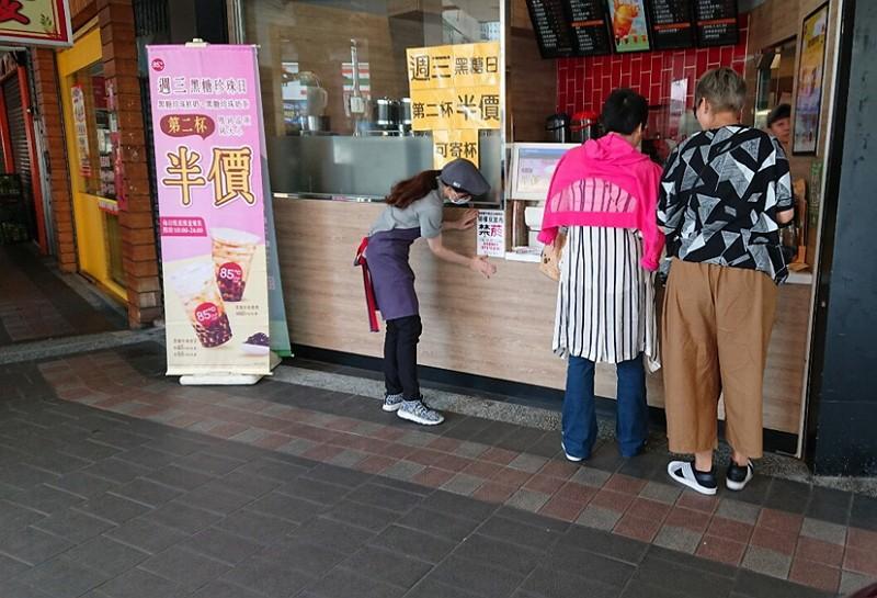 咖啡店店員配合政策貼上禁菸標語(圖/中央社/新北衛生局)