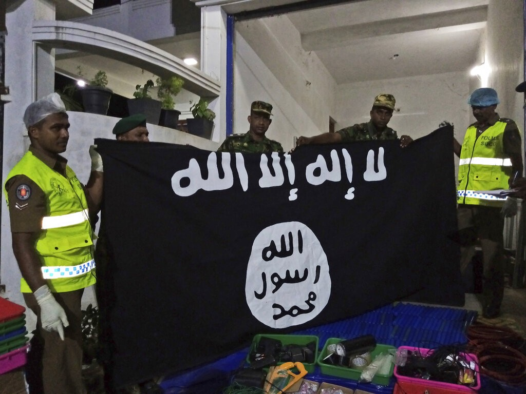 Sri Lankan police officers show ISIS flag recovered from alleged hideout of militants, in Kalmunai, in Eastern Sri Lanka.
