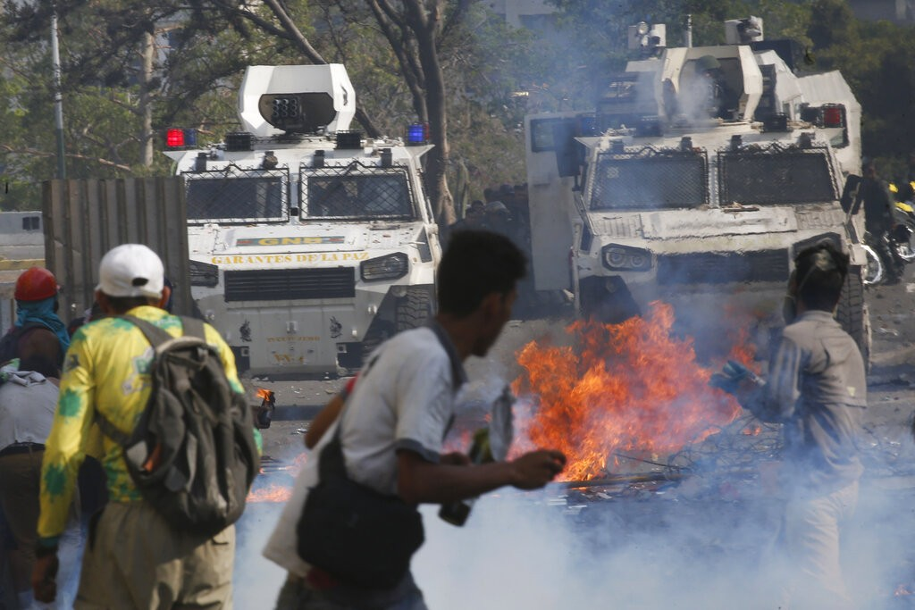 Opponents to Venezuela's President Nicolas Maduro face off with Bolivarian National Guards in armored vehicles who are loyal to the president, during
