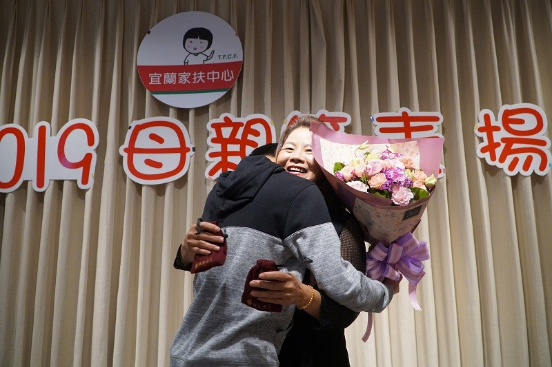 A boy, left, raised by 60-year-old single mother Wang Su-zhu, gives Wang a big hug during a ceremony to commend her on Sunday, May 5. (Taiwan Fund for...
