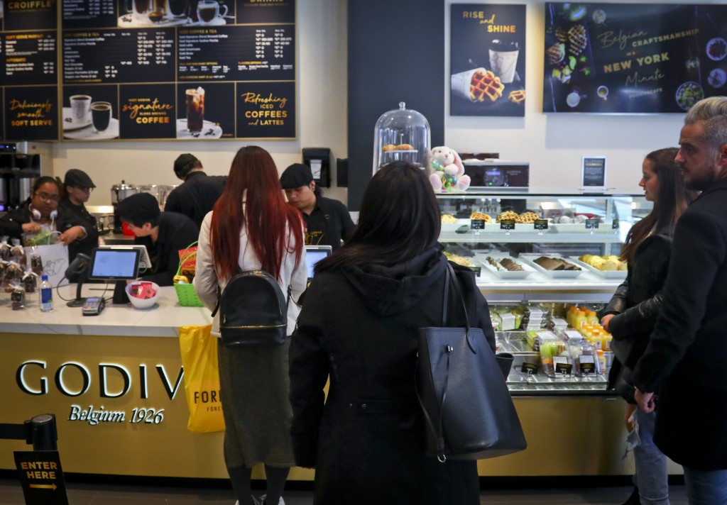 Customers wait in line for service at Godiva's new cafe in New York, Tuesday April 16, 2019. Godiva, the private Belgium chocolate maker, is looking b