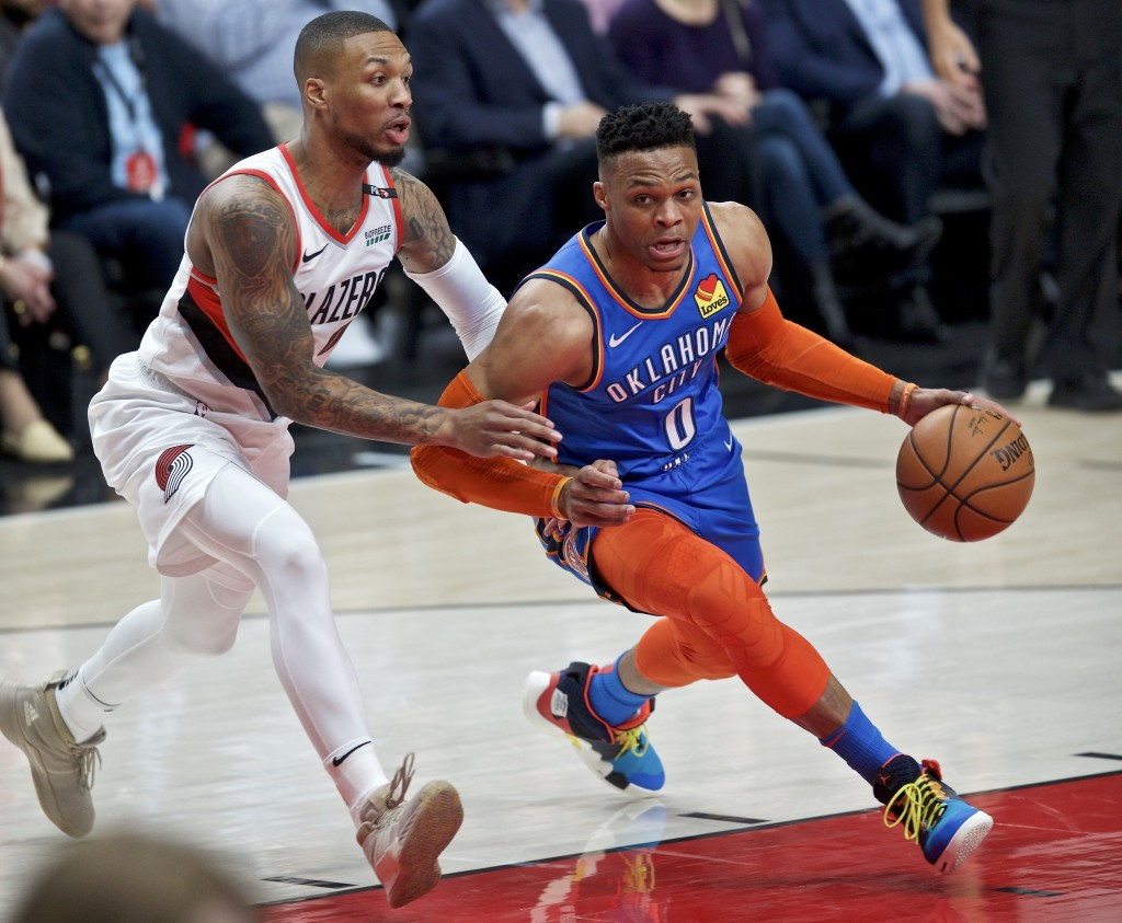 Oklahoma City Thunder guard Russell Westbrook, right, dribbles past Portland Trail Blazers guard Damian Lillard during the first half of Game 2 of an