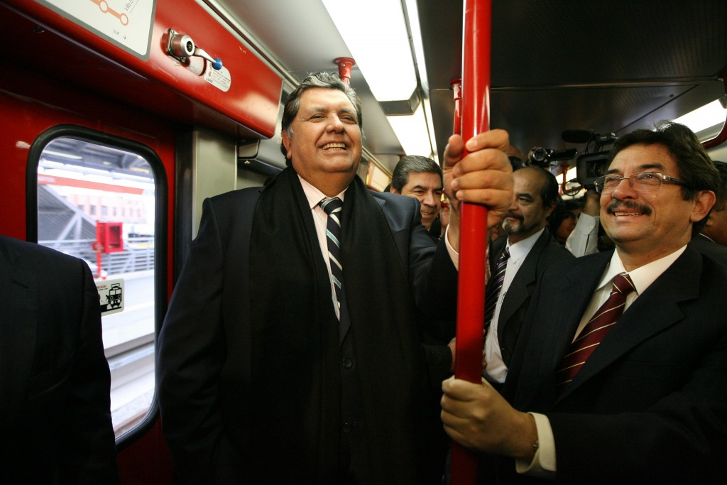 FILE - In this July 11, 2011 file photo, Peru's outgoing President Alan Garcia, left, ride the soon to be inaugurated Line 1 electrical train system i