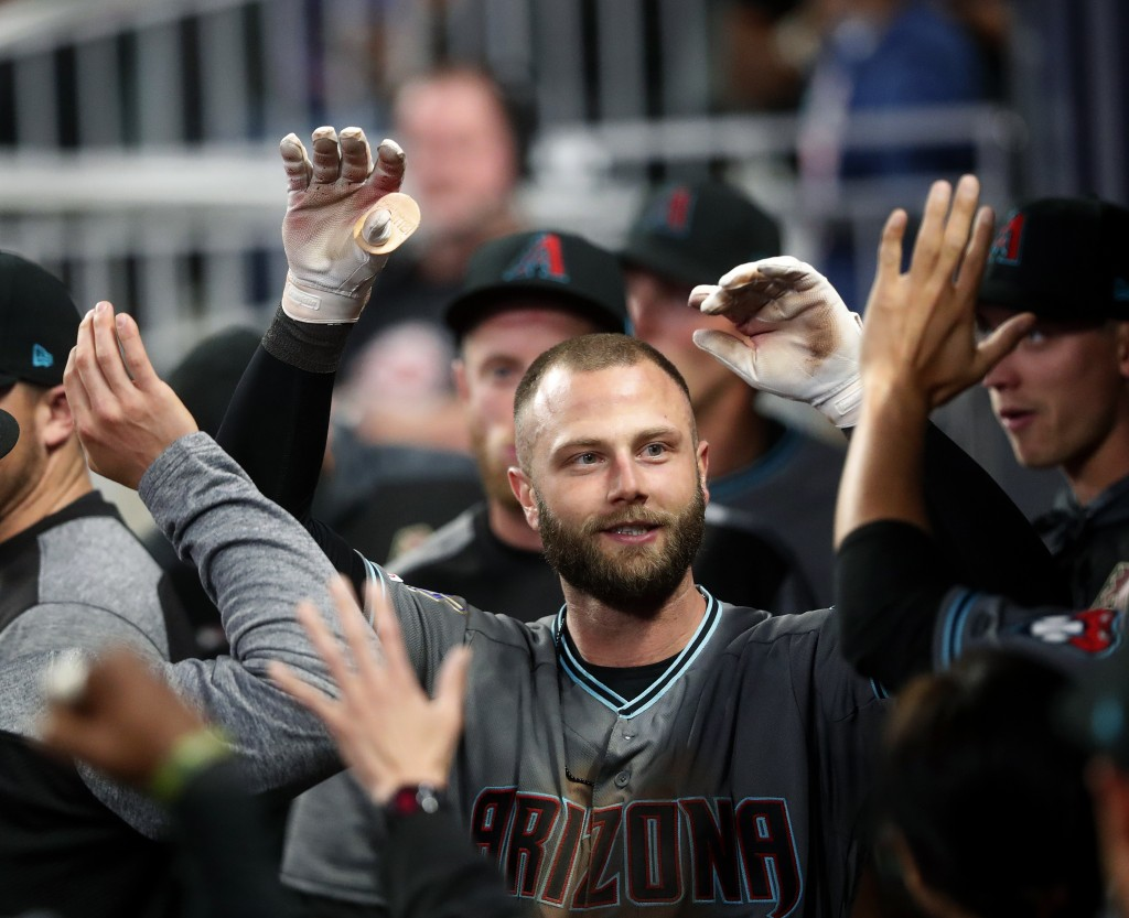 Arizona Diamondbacks' Christian Walker, left, celebrates in the dugout after hitting a solo-home run against the Atlanta Braves in the ninth inning of...