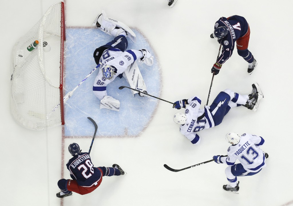 Columbus Blue Jackets' Oliver Bjorkstrand, bottom left, of Denmark, scores against Tampa Bay Lightning's Andrei Vasilevskiy, of Russia, during the sec