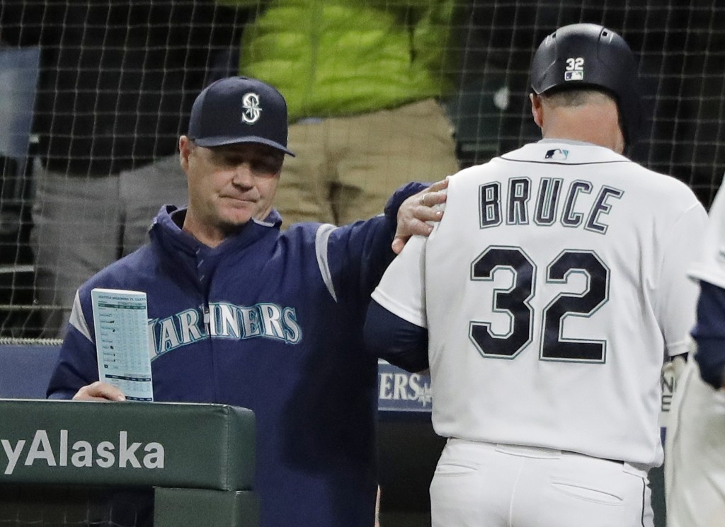 Seattle Mariners' Jay Bruce is greeted by manager Scott Servais, left, at the dugout after Bruce hit a solo home run during the eighth inning of a bas