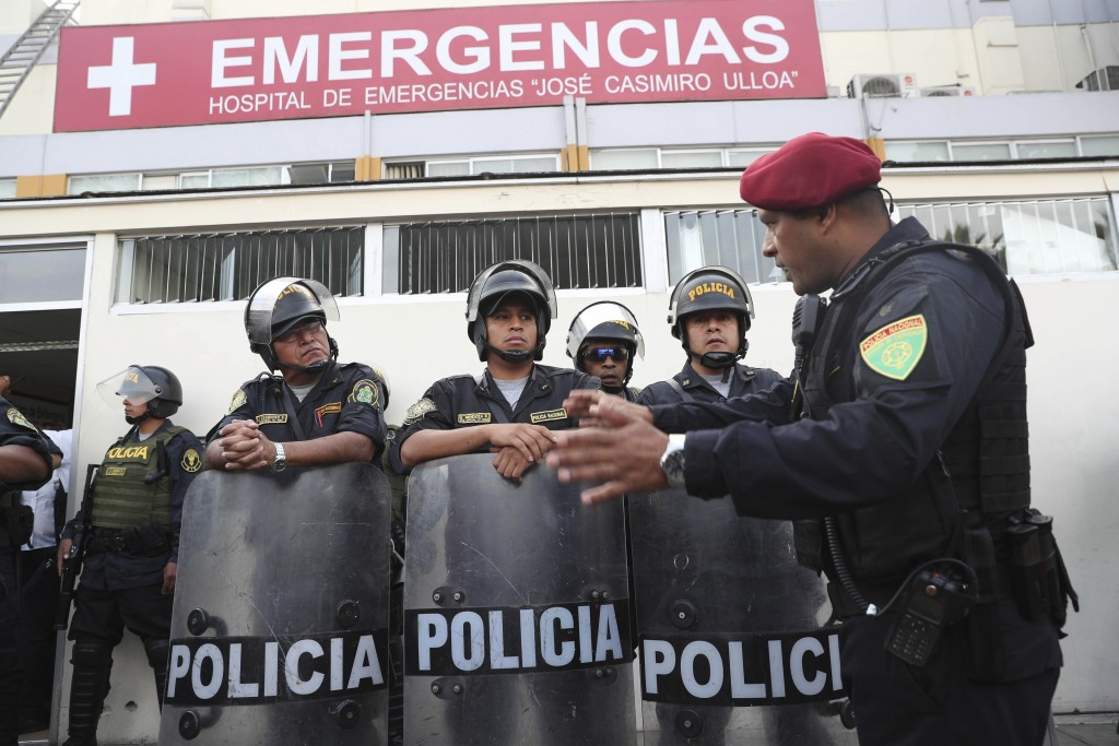 Peru's police officers stand guard at the emergency hospital Casimiro Ulloa where former Peruvian President Alan Garcia was taken after he shot himsel
