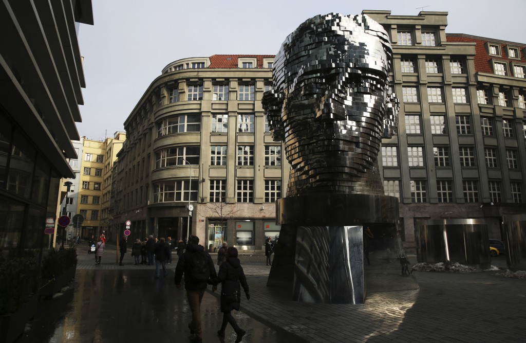 FILE -  In this Feb. 4, 2017 file photo, tourists walk past a moving metal sculpture of writer Franz Kafka in his birth city of Prague, Czech Republic