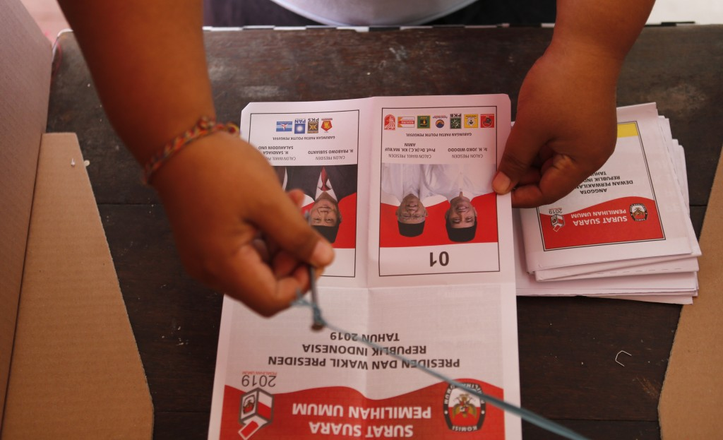 An Indonesian woman casts her vote during presidential and legislative elections at a polling station in Bali, Indonesia Wednesday, April 17, 2019. Vo...