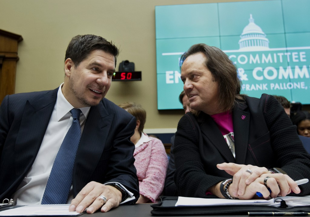 FILE - In this Feb. 13, 2019, file photo, Sprint Corporation Executive Chairman Marcelo Claure, left, speaks with T-Mobile US CEO and President John L