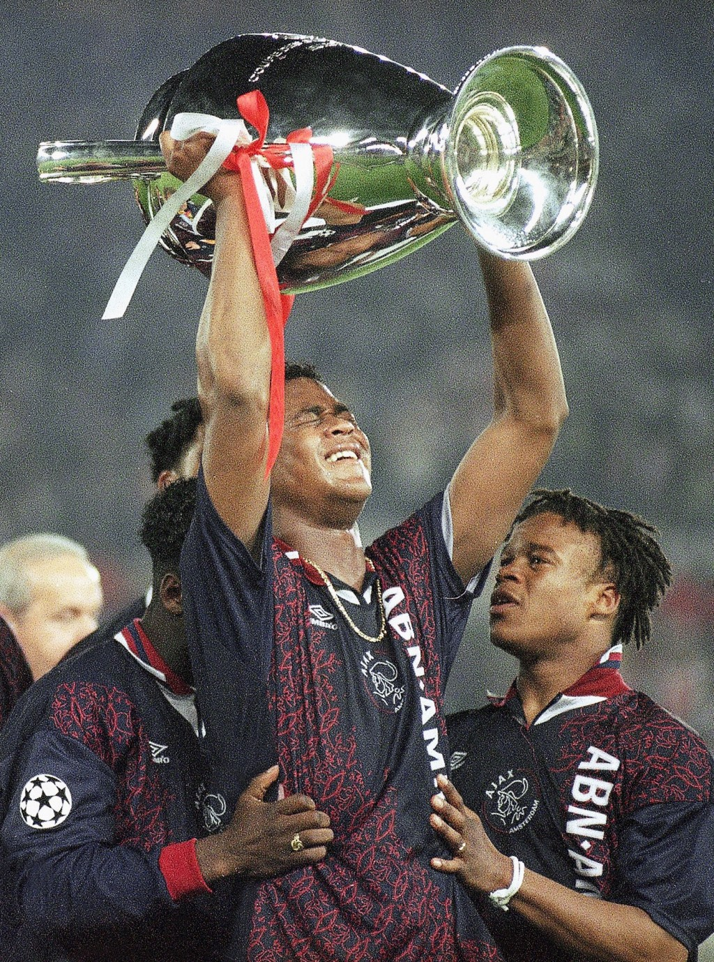 FILE - In this Wednesday, May 24, 1995 file photo, Ajax's Patrick Kluivert, center, who scored the only goal of the match holds the trophy in joy afte