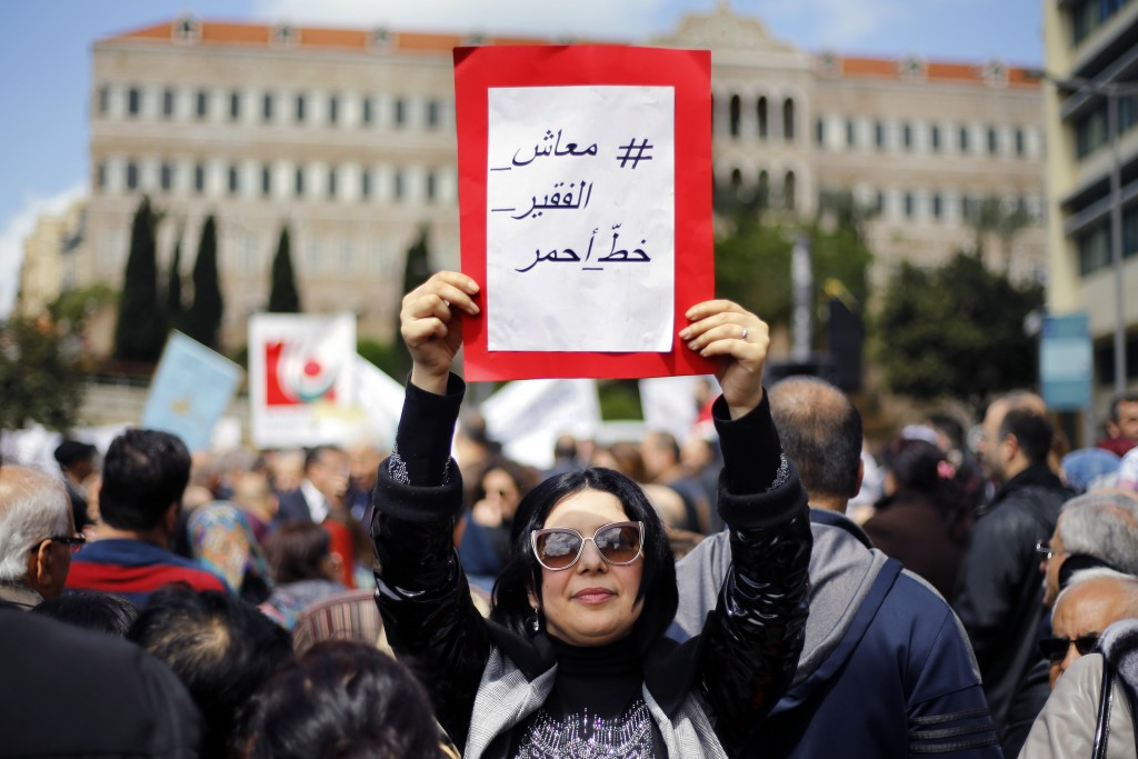 """A protester holds a placard with Arabic that reads, """"Salary of the poor is a red line,"""" in front of the government building during a parliament sessio"""