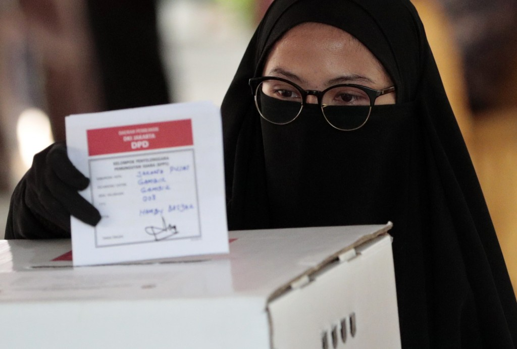 A Muslim woman casts her ballot during the election at a polling station in Jakarta, Indonesia, Wednesday, April 17, 2019. Voting is underway in Indon
