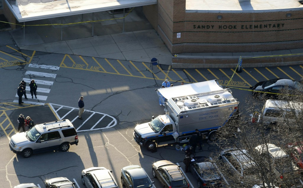 FILE - In this Dec. 14, 2012, aerial file photo, officials stand outside of Sandy Hook Elementary School in Newtown, Conn., where gunman Adam Lanza op