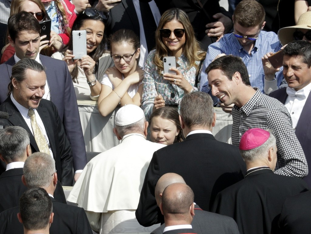 Pope Francis, back to camera, greets Swedish teenage environmental activist Greta Thunberg, center, during his weekly general audience in St. Peter's ...