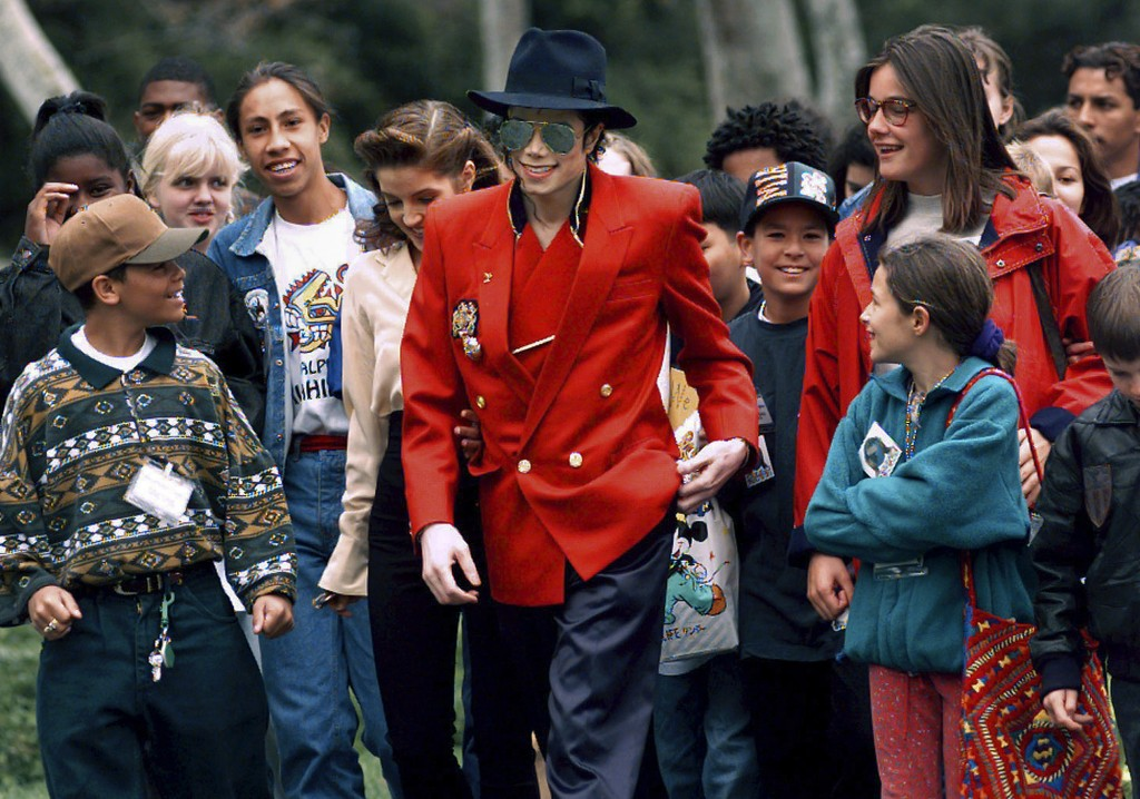 FILE - In this April 18, 1995, file photo, pop star Michael Jackson and Lisa Marie Presley, behind him at left, walk with children that were invited g