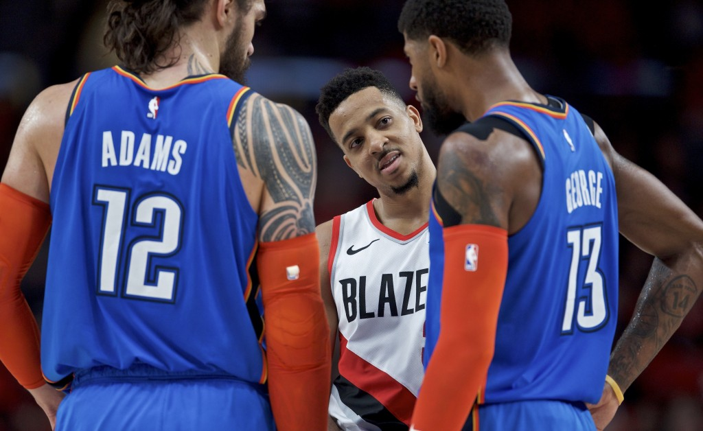Portland Trail Blazers guard CJ McCollum, center, talks to Oklahoma City Thunder forward Paul George, right, and center Steven Adams during the first