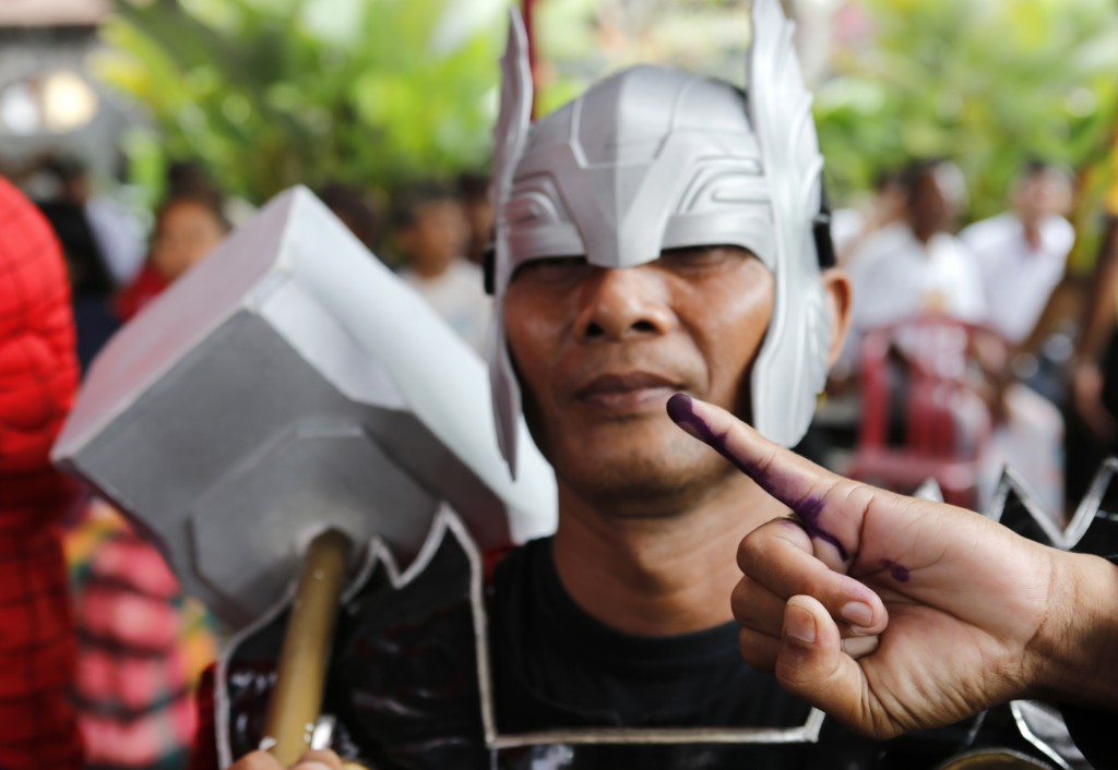 A man in Thor's costume shows his inked finger after casting at a polling station during election in Bali, Indonesia on Wednesday, April 17, 2019. Vot